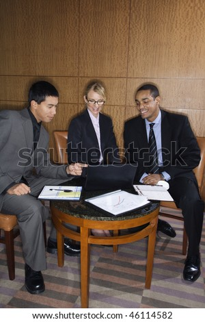 Three ethnically diverse business people sit at a small table and look at a laptop together. Vertical format.