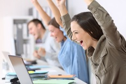 Three excited employees receiving good news on line in their laptops at office