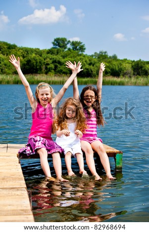 Three excited  girls sitting on the wooden bridge