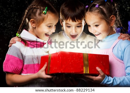 Three excited kids look happily into Christmas gift - stock photo