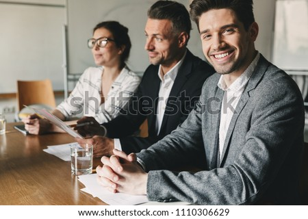 Three executive directors or head managers in formal suits sitting at table in office and interviewing new personnel for teamwork- business, career and placement concept