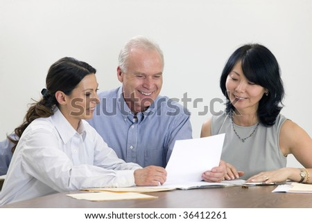 Three executives meeting over paperwork.