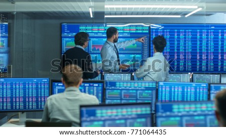 Three Experienced Stock Traders Talking Business, Consulting Documents and Argue About Data. They Work for a Big Stock Exchange Firm. Office is Full of Displays Showing Infographics and Numbers.