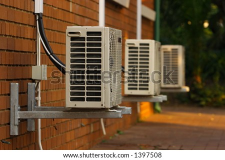 Three External Air Conditioner Units Mounted Outside On A