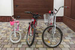 Three family bikes stand in the yard against the backdrop of the garage door