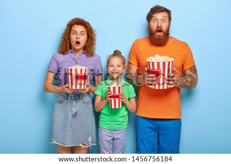 Three family members enjoy watching television at home, mother and father stare with frightened expressions at screen, their small daughter stands between and smiles, eat fast food. Omg, how scary!