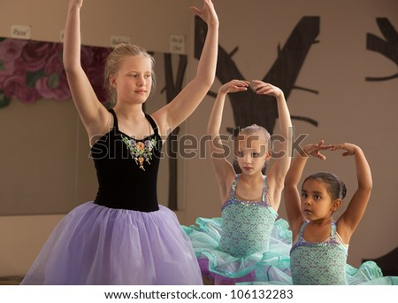 Three female dance students of different ages practicing together