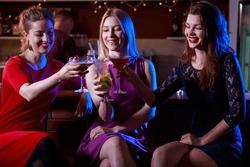 Three female friends enjoying drinking in the club