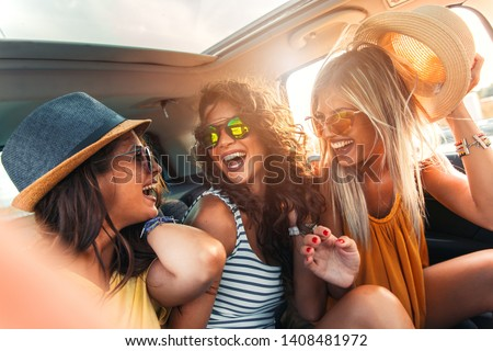 Three female friends enjoying traveling in the car. Sitting in rear seat and having fun on a road trip. #1408481972