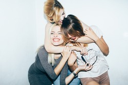 Three female friends posing in front of white wall