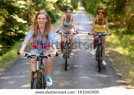 Three female friends riding bikes in park enjoy summer sport