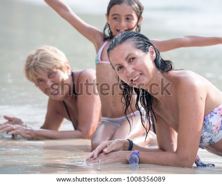 Three female generations happy and smiling, laying down on the shoreline.