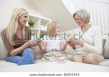 Three female generations of one family at home. Mother, grandmother and daughter who is playing at serving tea in a china tea set.
