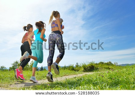 Three Female Joggers running together outdoors - Shutterstock ID 528188035