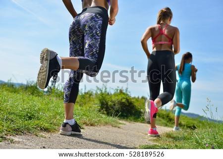 three female joggers running...