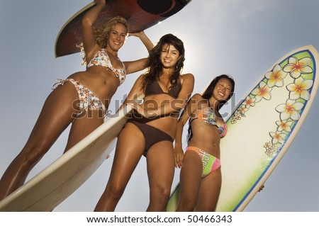 Three female surfers holding surfboards outdoors, low angle view