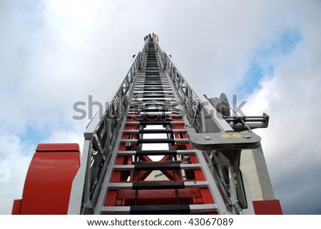 Three firefighters on a ladder of a fire truck. Photo taken from streetlevel.