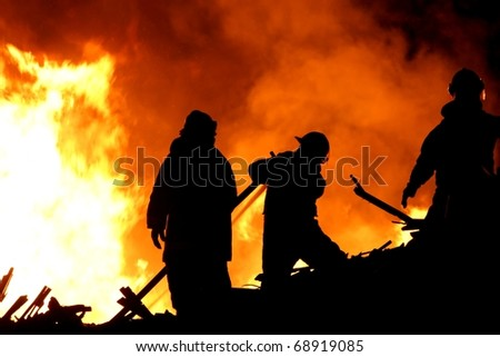 Three fireman in silhouette fighting a raging fire