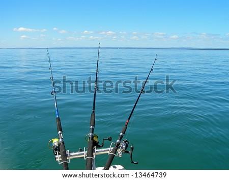 Three fishing rods cast into a blue calm sea.