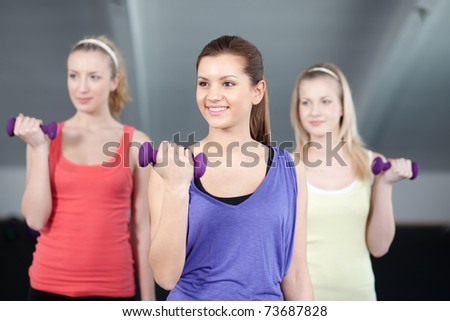 Three fit and beautiful young women lifting weights in a fitness club