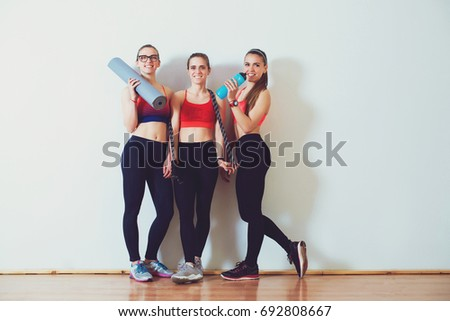 Three fitness young girls in sportswear standing against wall in fitness gym. Girls smiling and looking to the camera. #692808667