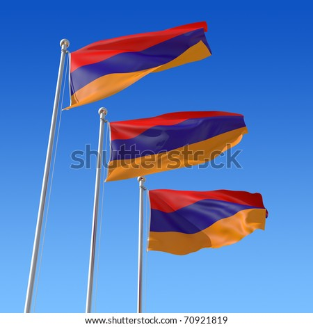Three flags of Armenia against blue sky.