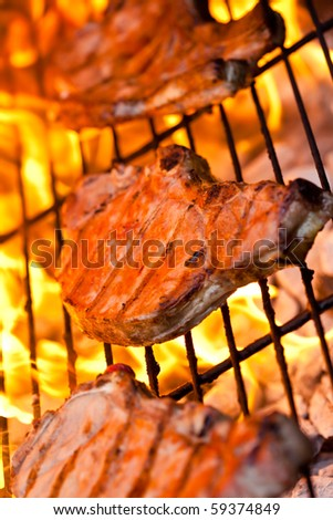 Three flamed grilled pork chops on the BBQ