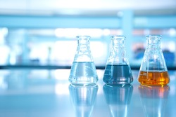 three flask of water black orange solution in science laboratory background