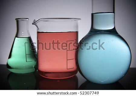 three flasks with colored liquid on a white back-light