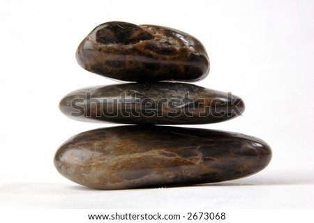 Three flat, dark-toned stones balanced