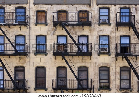 Three floors of windows with fire escapes on the facade of a New York apartment building that is in desperate need of paint and repairs.