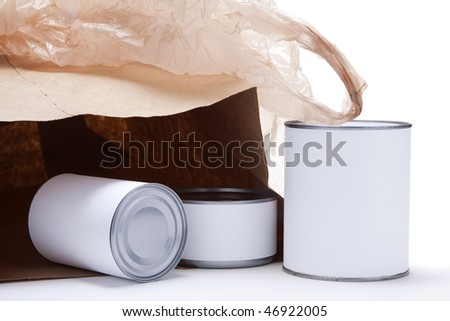 Three food cans with blank white labels in front of an open brown paper grocery bag with a brown plastic shopping bag on top.