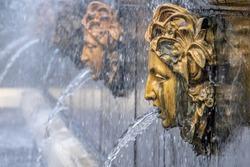 three fountains heads, gargoyle with water, drop on nose, blurred  background, Peterhof, Saint Petersburg, Russia.