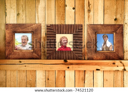 Three frames with family photos on wooden wall - stock photo
