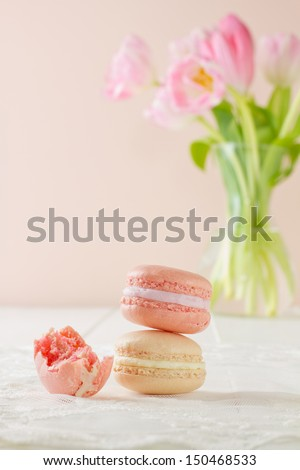 Three French macarons in stacked formation, on white wood table with lace placemat. One has had a bite taken out of it. Soft pink and white tulips sit in a vase in the background.