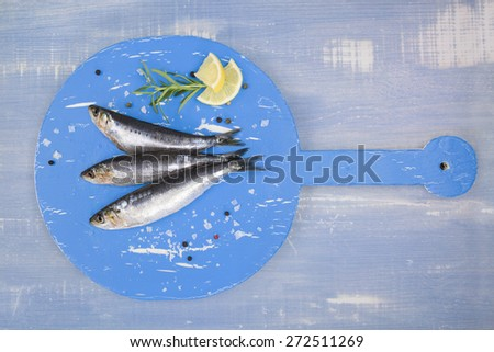 Three fresh anchovy fish on round blue wooden kitchen board on blue wooden table, top view. Culinary seafood concept. Delicious healthy eating.