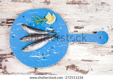 Three fresh anchovy fish on round blue wooden kitchen board on white and brown wooden table, top view. Culinary seafood concept. Delicious healthy eating.