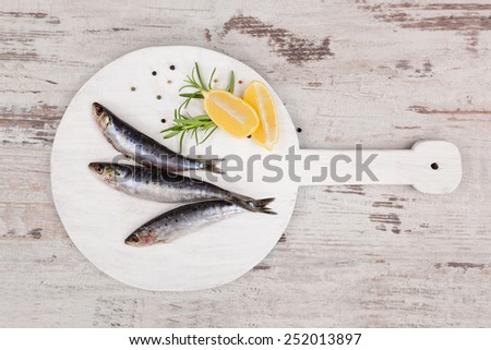 Three fresh anchovy fish on white round kitchen board on white wooden table, top view. Culinary seafood concept. Delicious healthy eating.