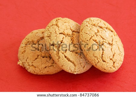 three fresh appetizing oatmeal cookies over red background