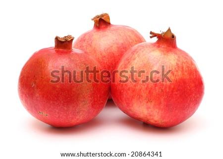 Three fresh appetizing pomegranates on white background