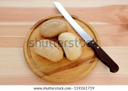 Three fresh bread rolls with a knife on a wooden board