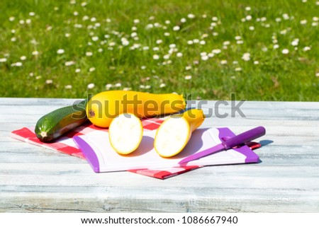Three fresh courgette on rustic bright wooden table with natural green background. One of the yellow zucchini was freshly sliced on an cutting board. Concept health. #1086667940