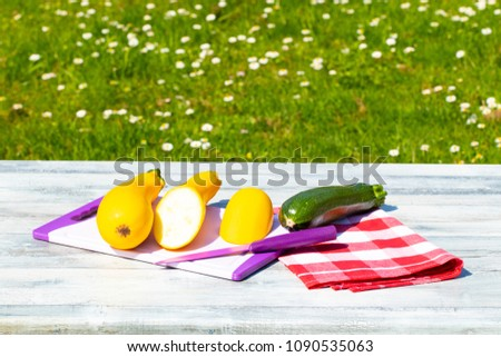 Three fresh courgette on rustic bright wooden table with natural green background. One of the yellow zucchini was freshly sliced on an cutting board. Concept health. #1090535063