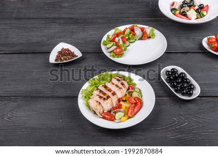 Three fresh delicious salads with chicken, tomato, cucumber, onions and greens with olive oil. Summer menu salads