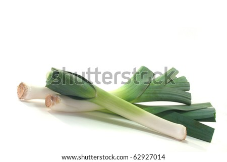 three fresh leeks on a white background
