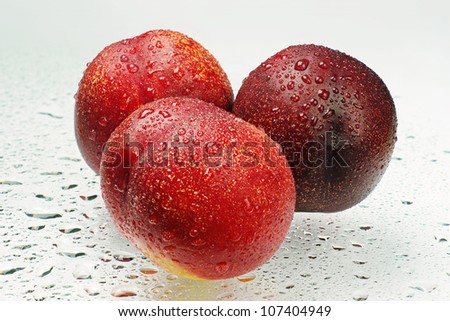 Three fresh nectarines with water drops