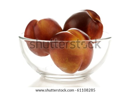 three fresh picked nectarines in a glass bowl, isolated on white