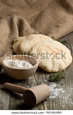 Three fresh pitas bread, thyme and bowl of flour on old wooden table