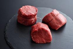 Three fresh raw Prime Black Angus Tenderloin beef steaks on stone background. Selected focus.