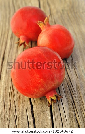 Three fresh red pomegranate on a wooden board